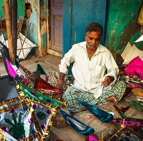 Kite-maker-sitting-cross-legged-on-the-floor-surat